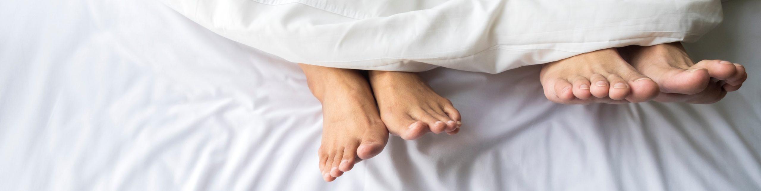 Pieds d'un couple dans un lit confortable